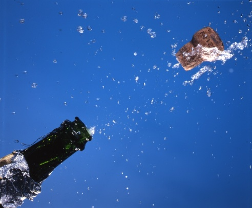 champagne-cork-popping-flying-water-liquid-drops-on-blue-ajhd.jpg